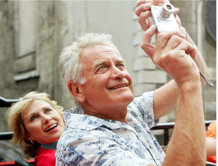 Older man and woman taking a photo while on a tour