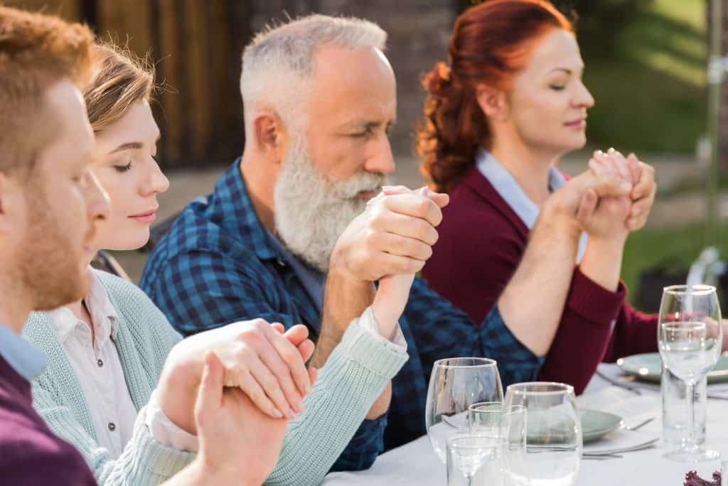 Family members holding hands at dinner table