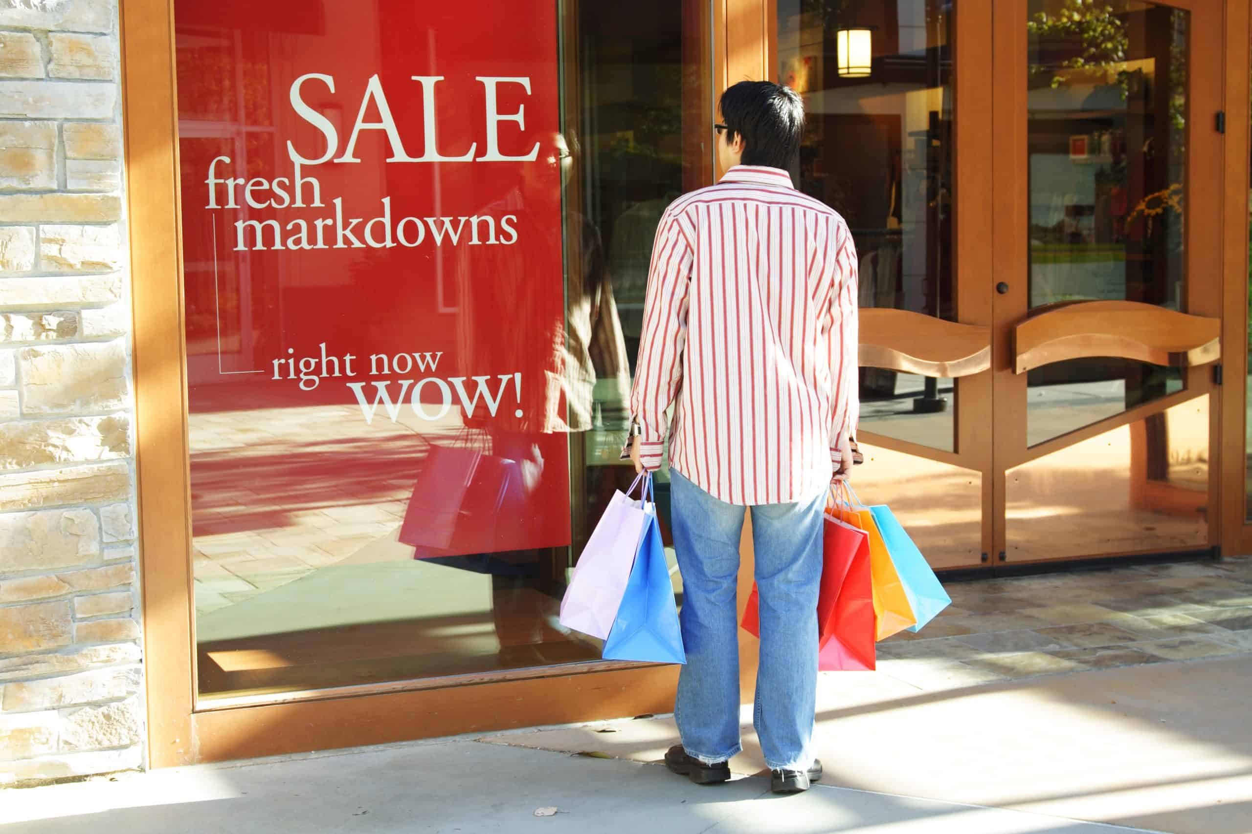 End of quarter bargains - Man with shopping bags looking at store sale sign