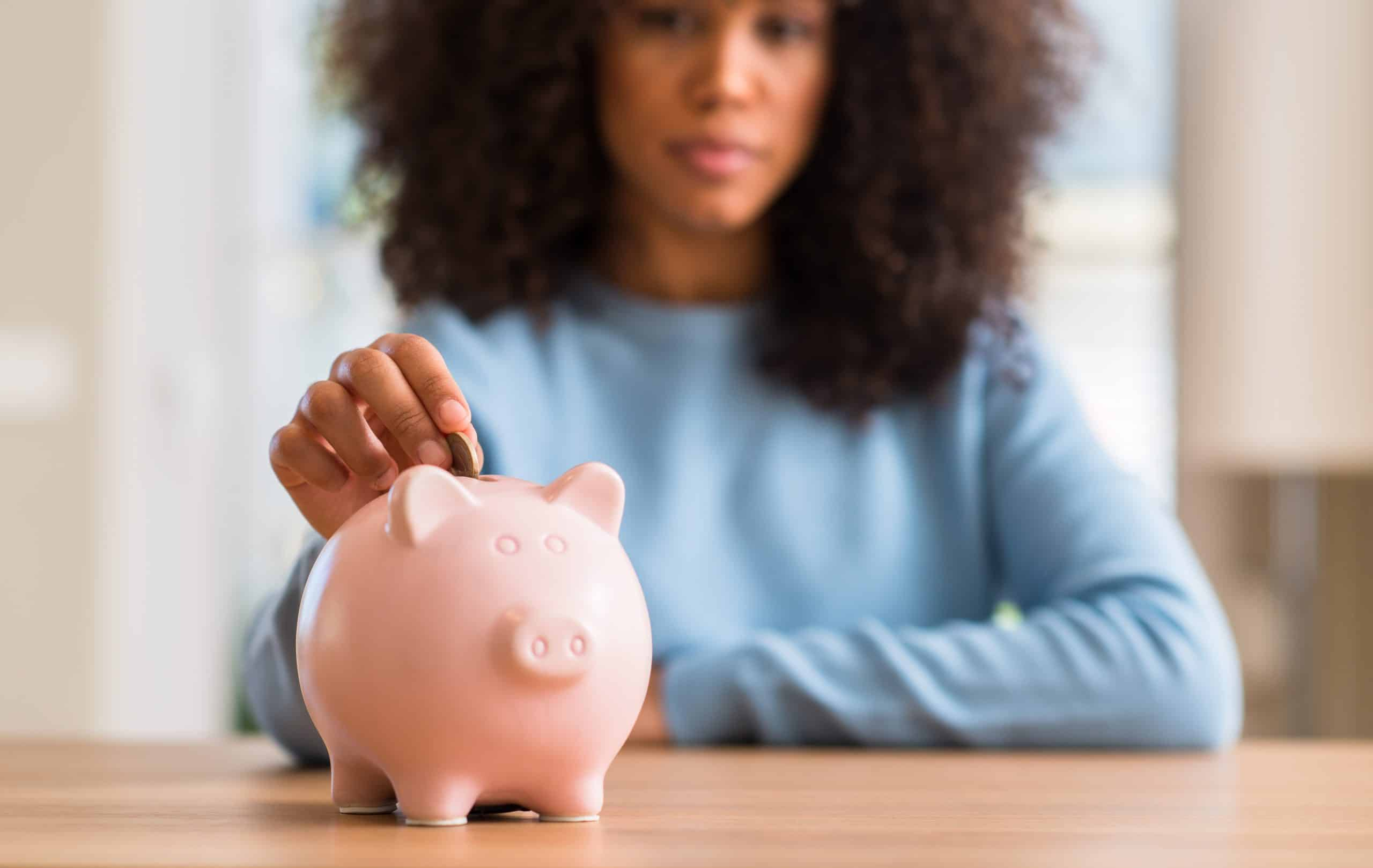 How to build an emergency fund - African american woman saves money in piggy bank with a confident expression on smart face thinking serious