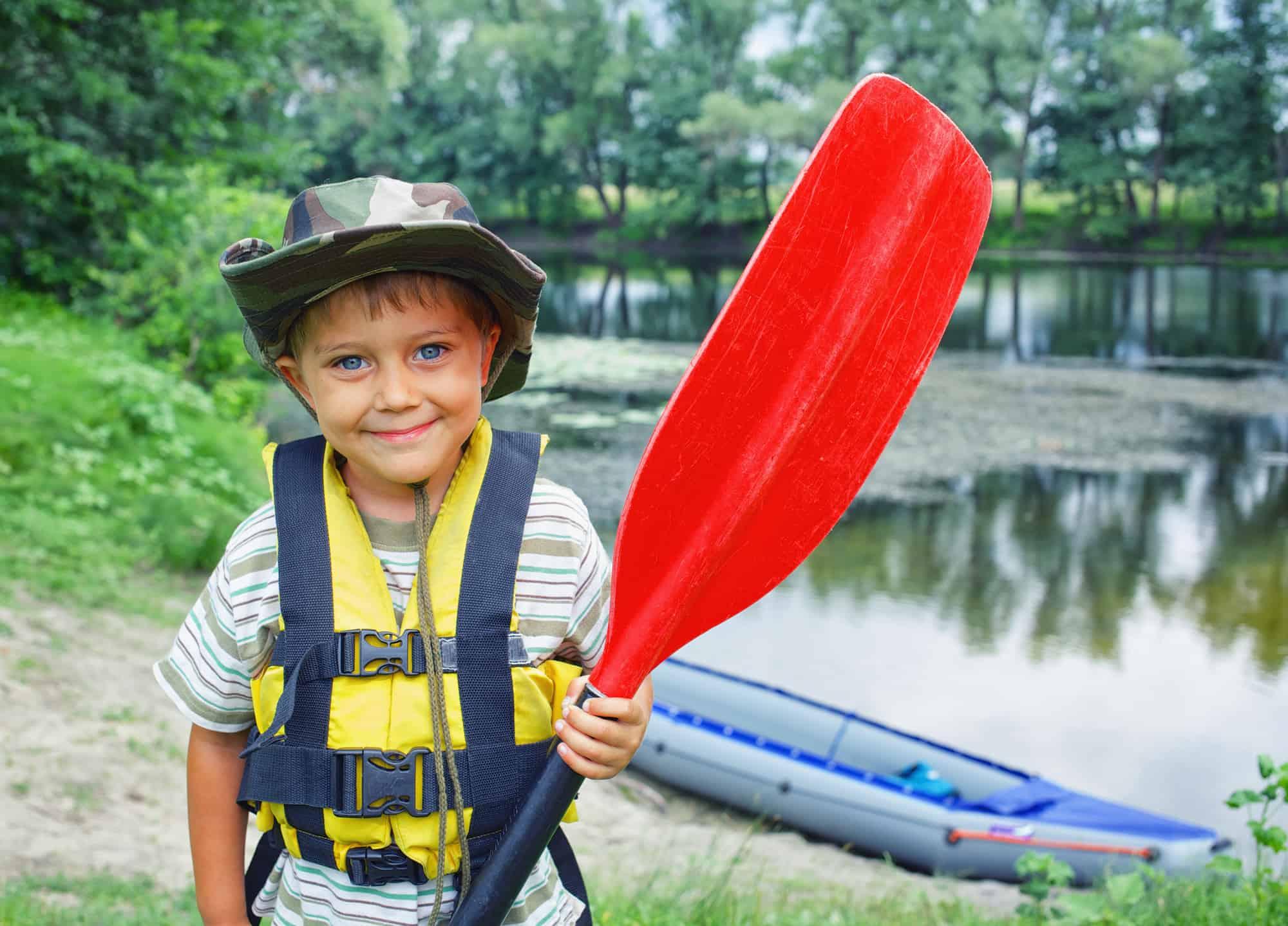 happy boy holding paddle near kayak at summer camp
