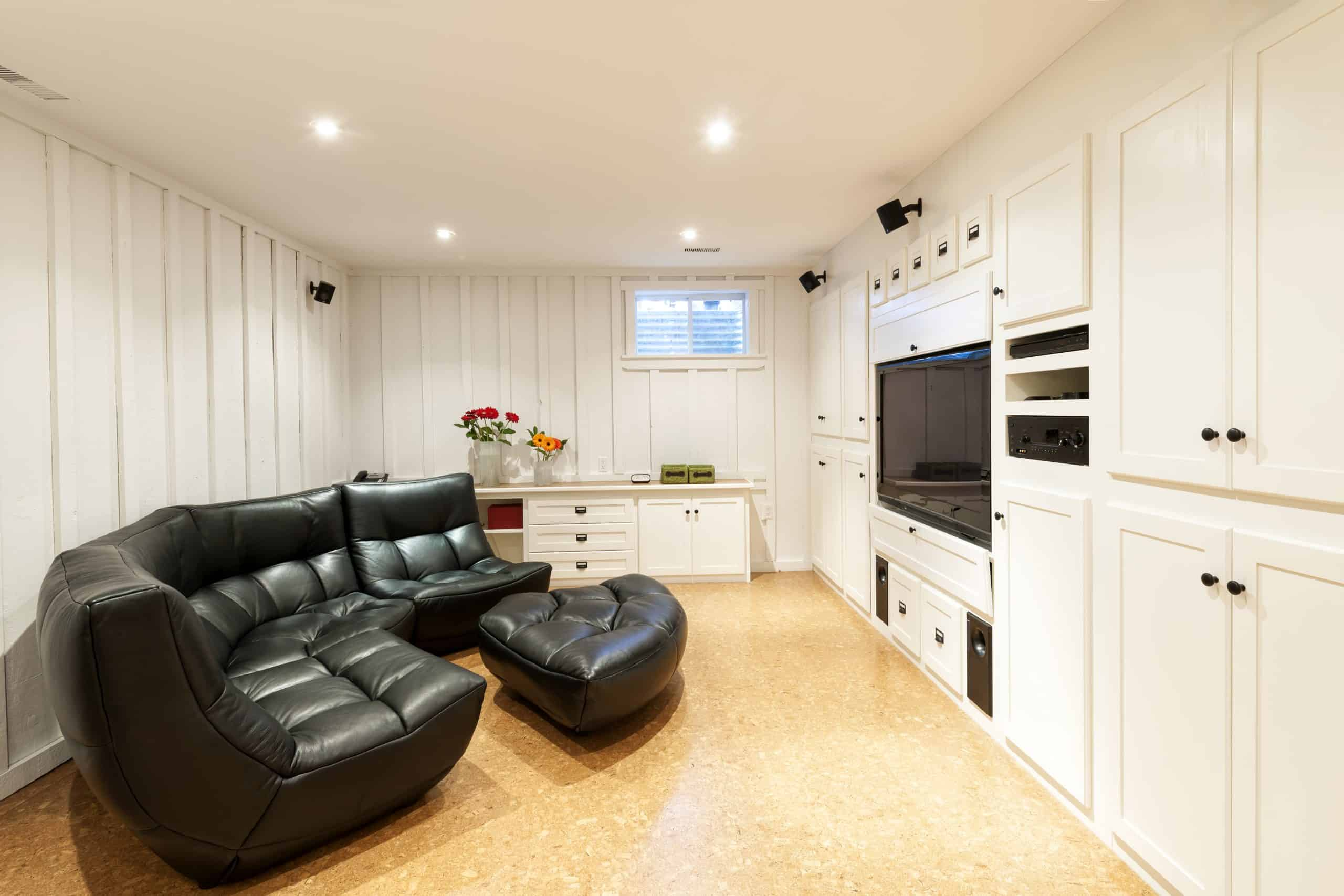 Home renovations that add value - finished basement with leather couch, flat-screen TV, and built-in cupboards