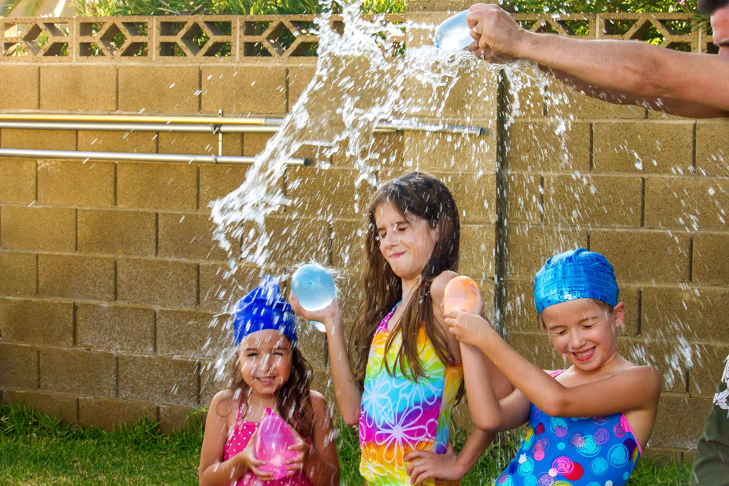 DIY water toys - Dad breaks water balloon over three girls in colorful bathing suits and swim caps holding water balloons