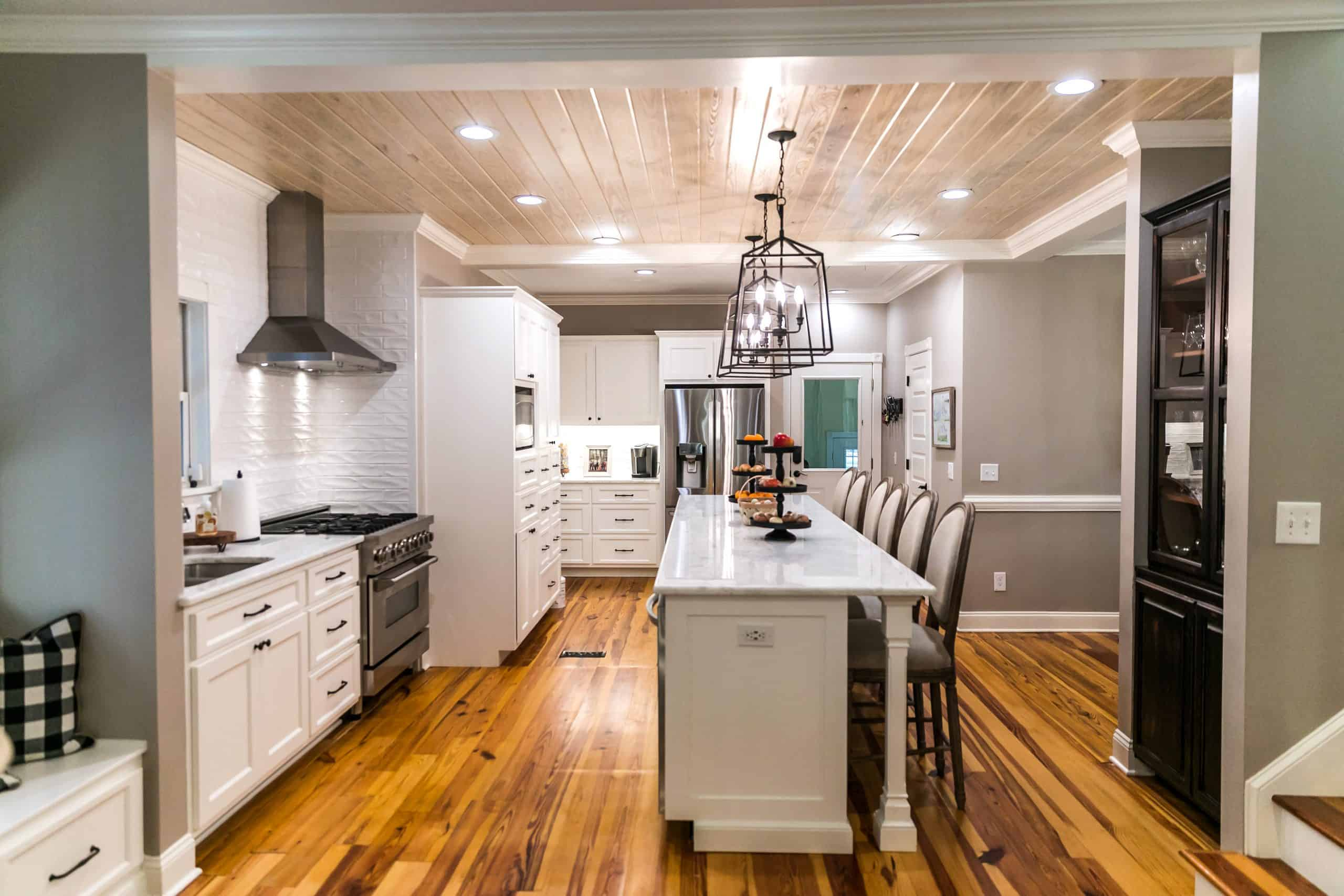 Remodel kitchen for less - Large renovated white kitchen with updated cabinets, textured subway tile, black iron lights and pine hardwood flooring