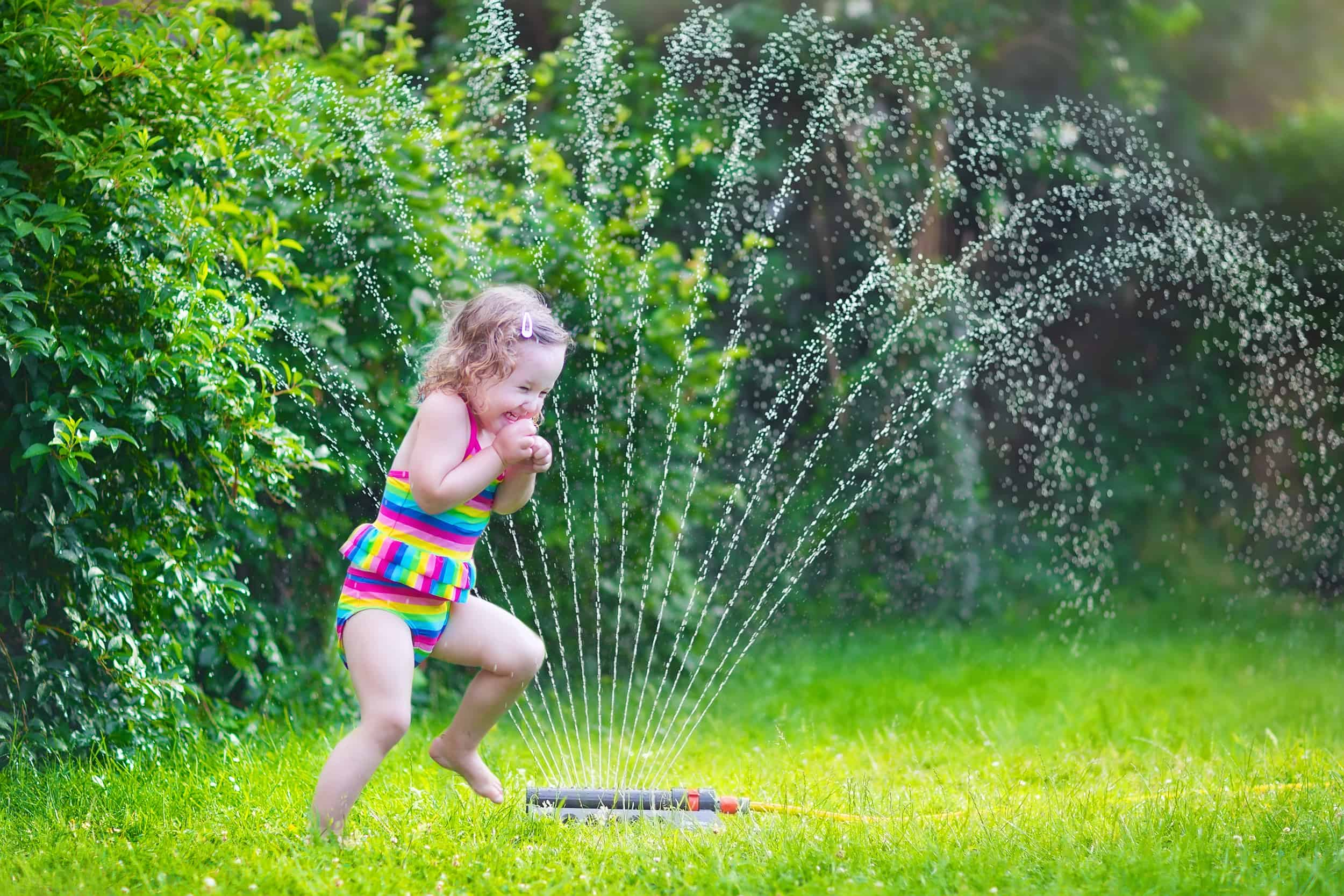 Cheap DIY water toys - Funny laughing little girl in a colorful swimming suit running though garden sprinkler playing with water splashes having fun in the backyard on a sunny hot summer vacation day