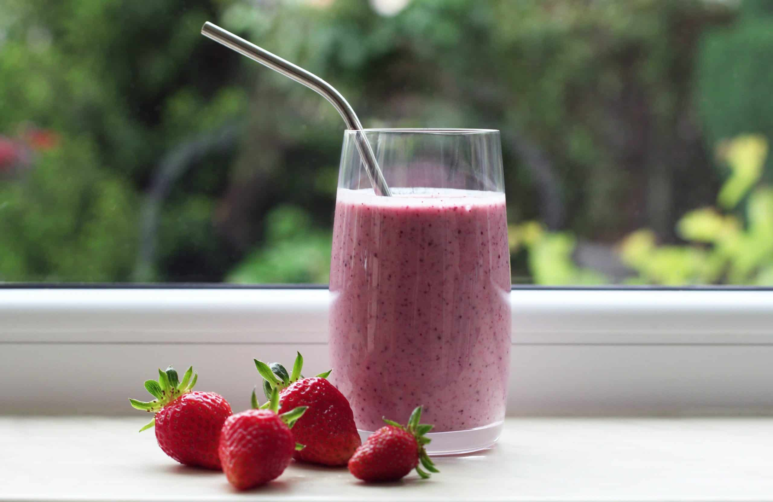DIY smoothie recipes - Glass with pink smoothie surrounded by fresh strawberries, set by window looking out onto greenery