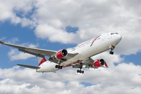 Earn miles and points to travel for less - airplane taking off against blue sky with white clouds