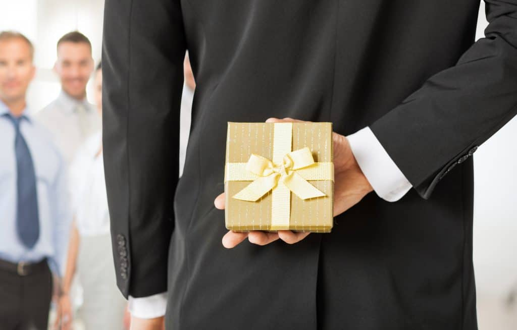 man hands holding gift box in office