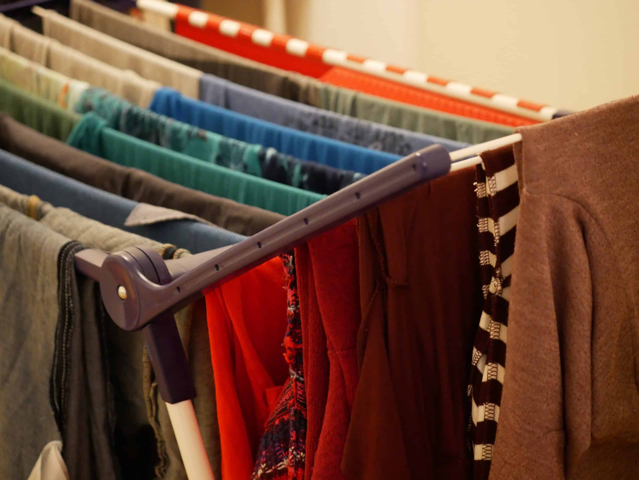 save money on laundry - colorful clothes draped over laundry drying rack
