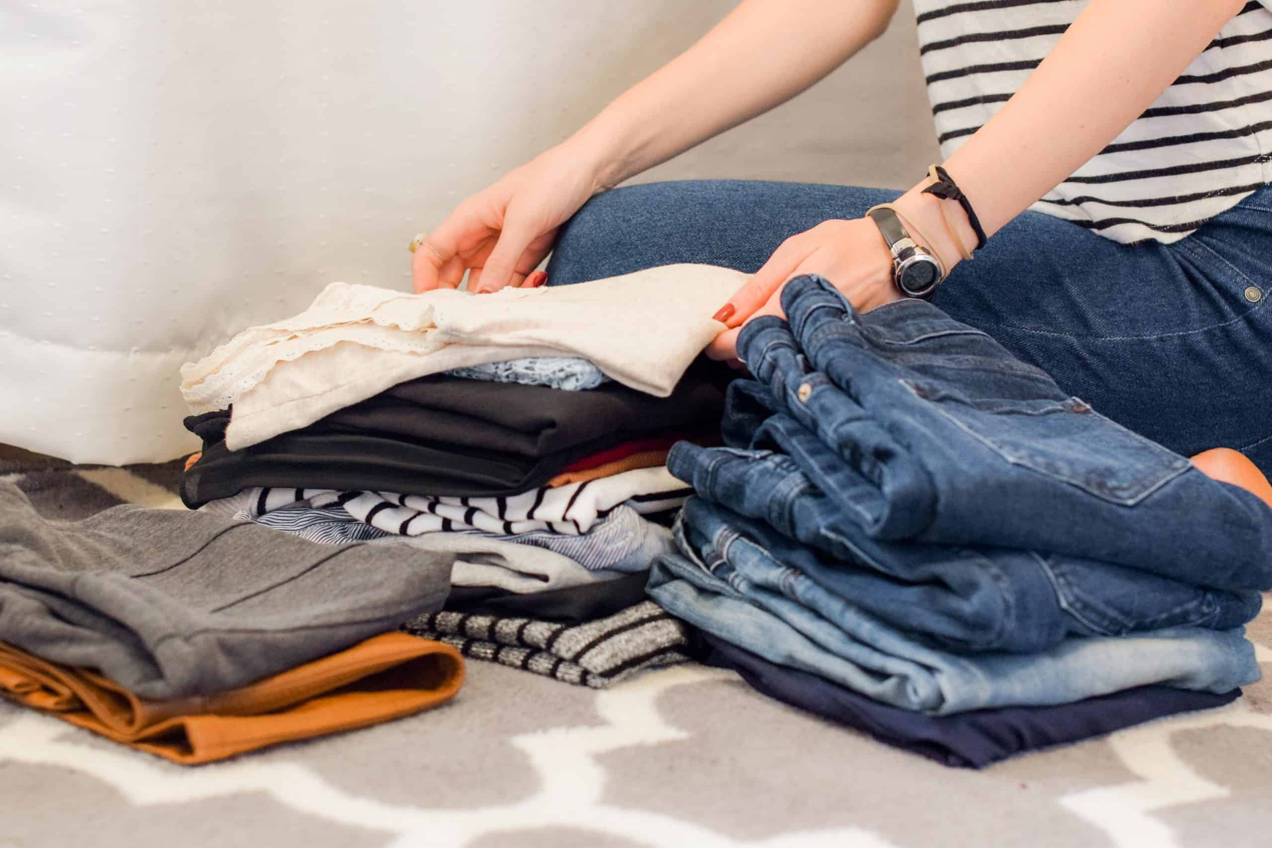 save money on laundry - woman folding clean clothes