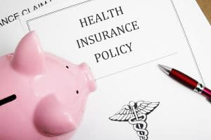 piggy bank with health insurance policy