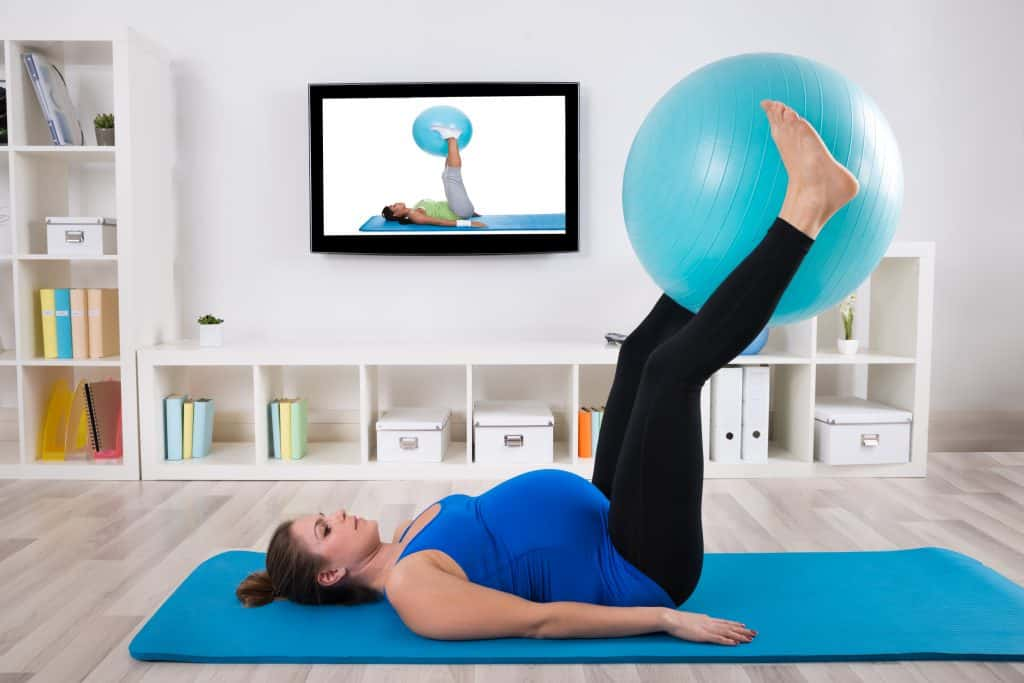Pregnant Female Exercising With Fitness Ball yoga dvd
