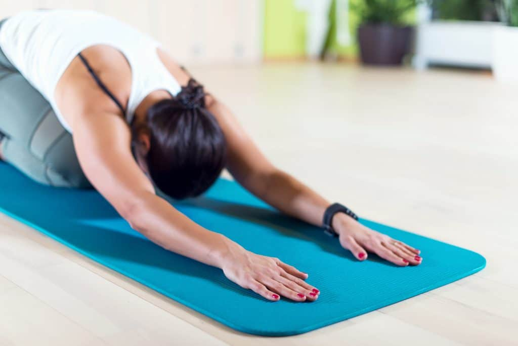 Fit woman doing stretching pilates exercises in fitness studio yoga
