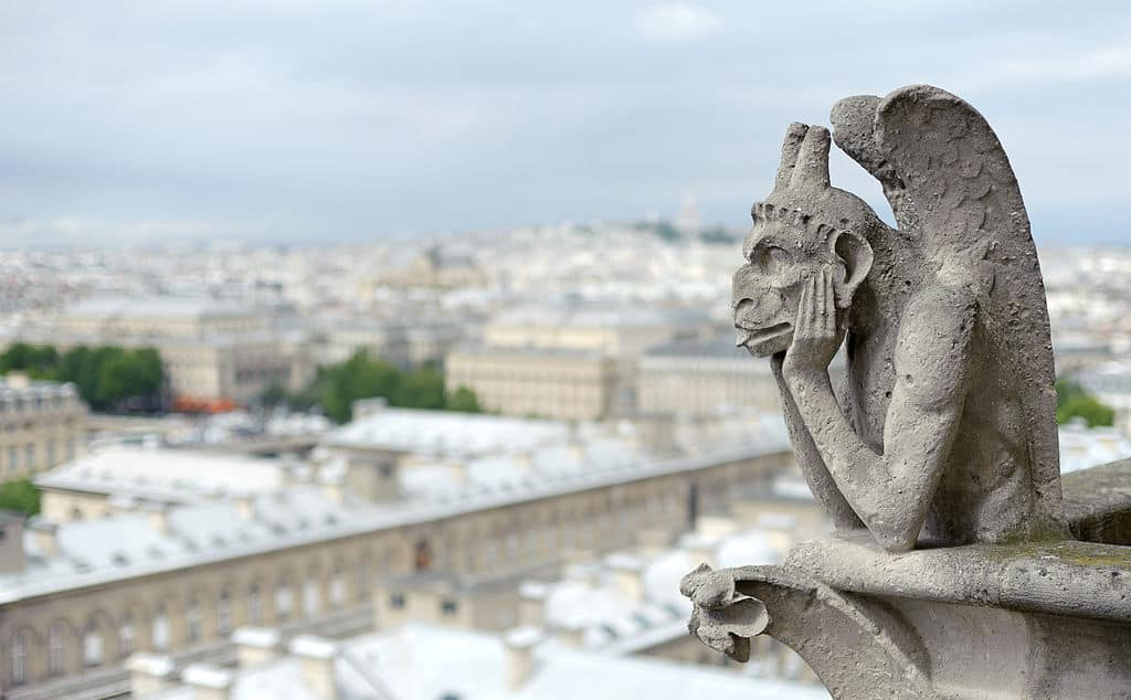 Bored Gargoyle knows how to kill time at Notre Dame de Paris