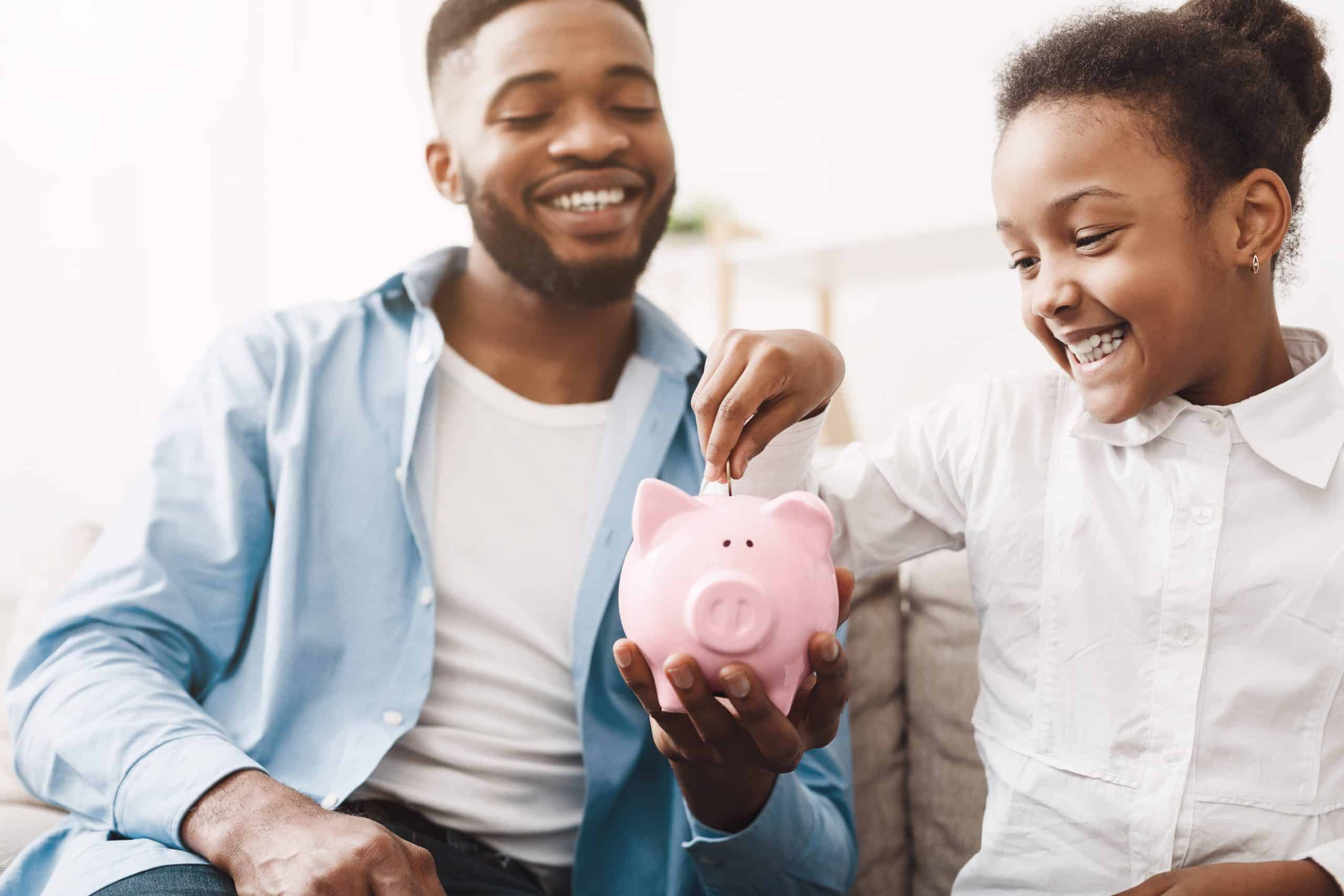 Teach kids about money - Dad holds piggy bank while daughter puts in a coin