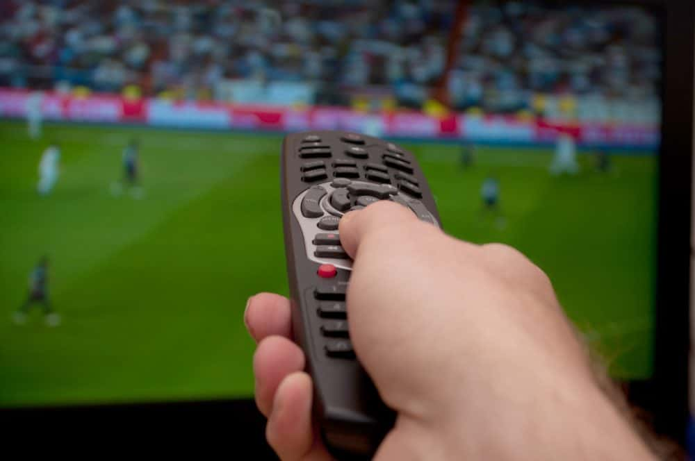 tv coverage of live sports with a hand holding a remote control in front of the screen