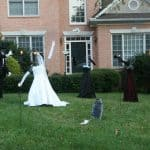 Haunted Wedding Halloween Yard Decor - seemingly headless groom, bride, and guests in a graveyard on the lawn of a house