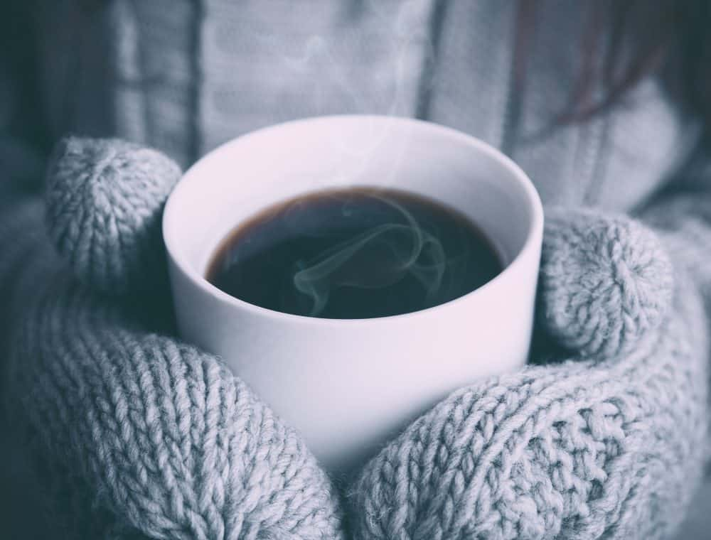 person holding mug of tea in hands with mittens