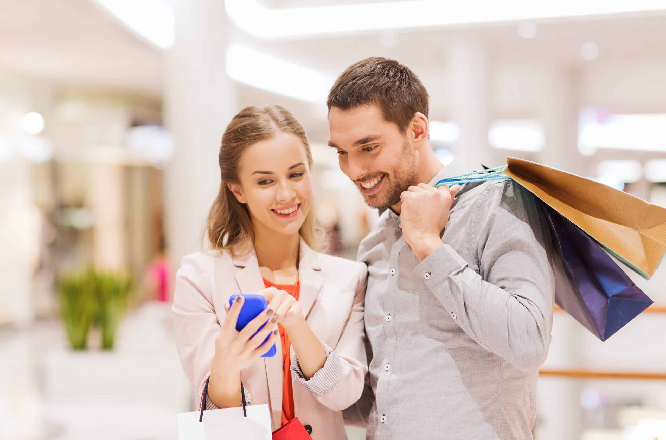 Best money-saving shopping apps - Man and woman find deals on phone apps when shopping at the mall