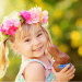 little girl with pink flowers in hair holding chocolate bunny