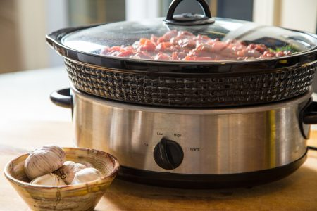 Meal cooking in slow cooker on counter