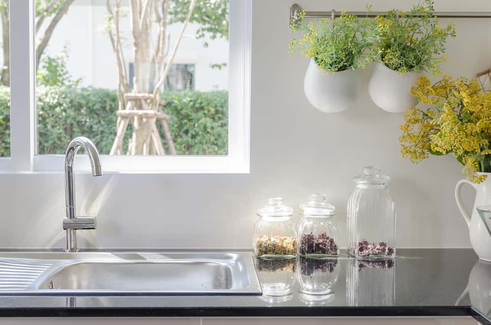 Save thousands around the house - modern sink on black kitchen counter with plants