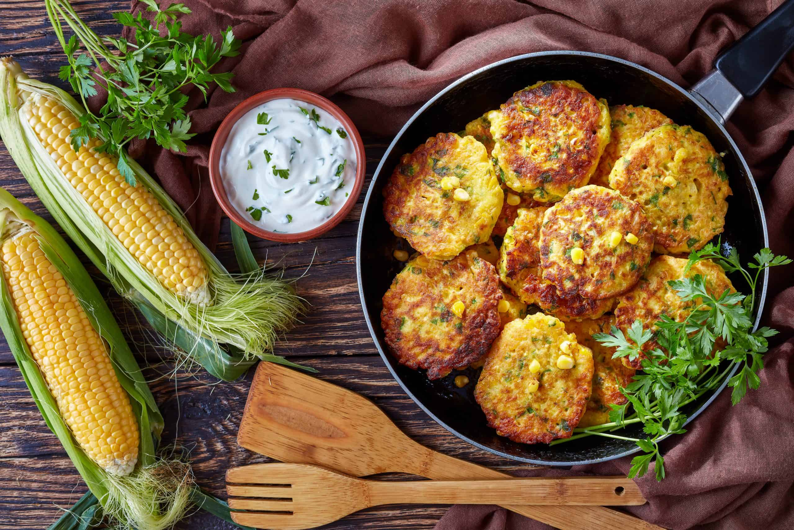 Sweet corn recipes - corn fritters in a skillet with yogurt dipping sauce and fresh sweet corn in cobs on an old wooden kitchen table