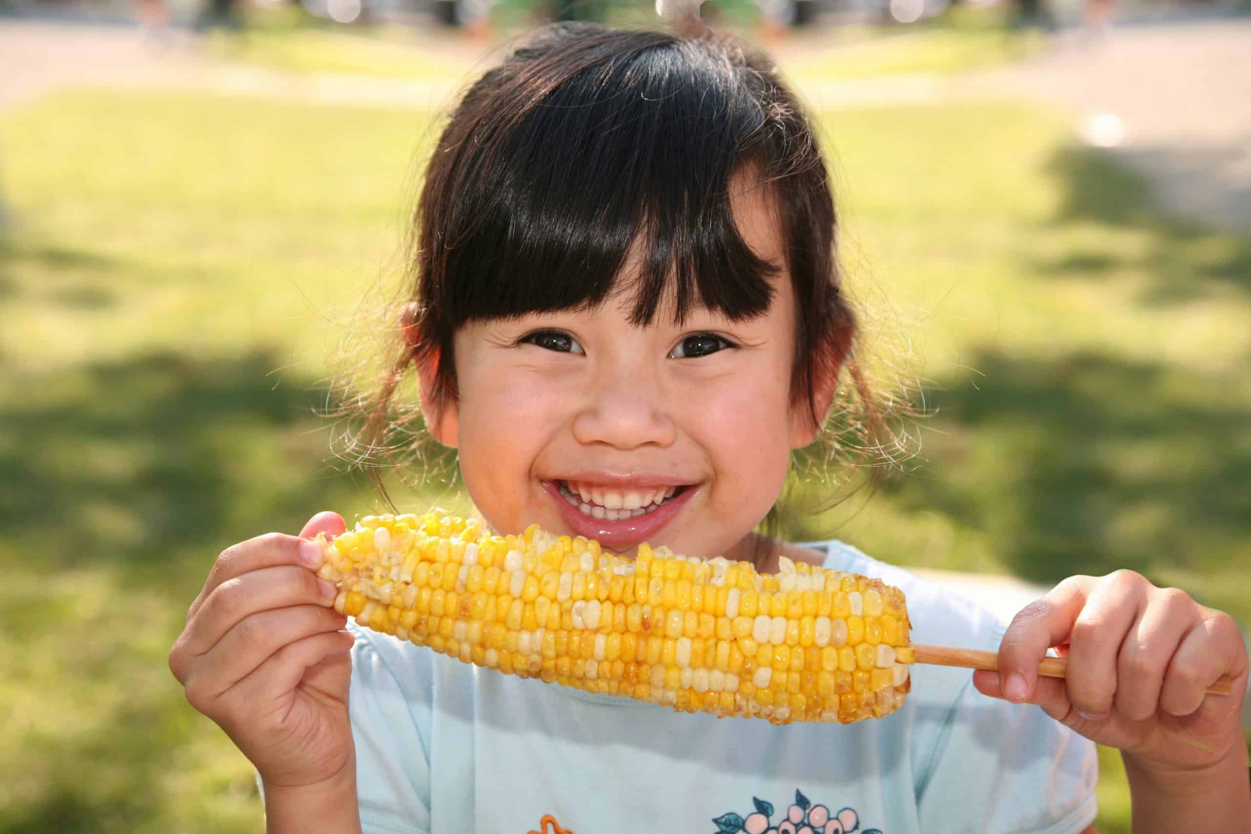 Sweet corn recipes - Asian girl with dark hair in park smiling while eating corn on the cob