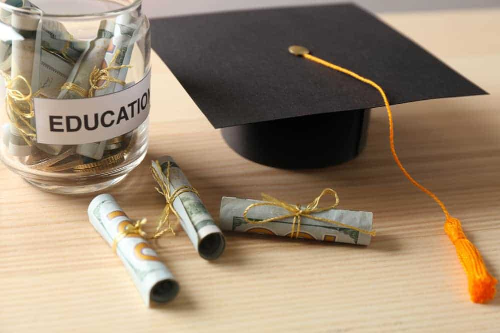 """jar marked """"education"""" filled with money; mortarboard next to it"""