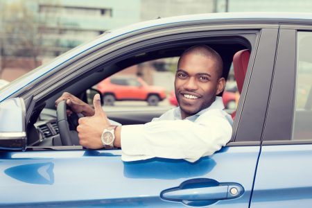 Save money on gas - Black man in blue car giving thumbs up
