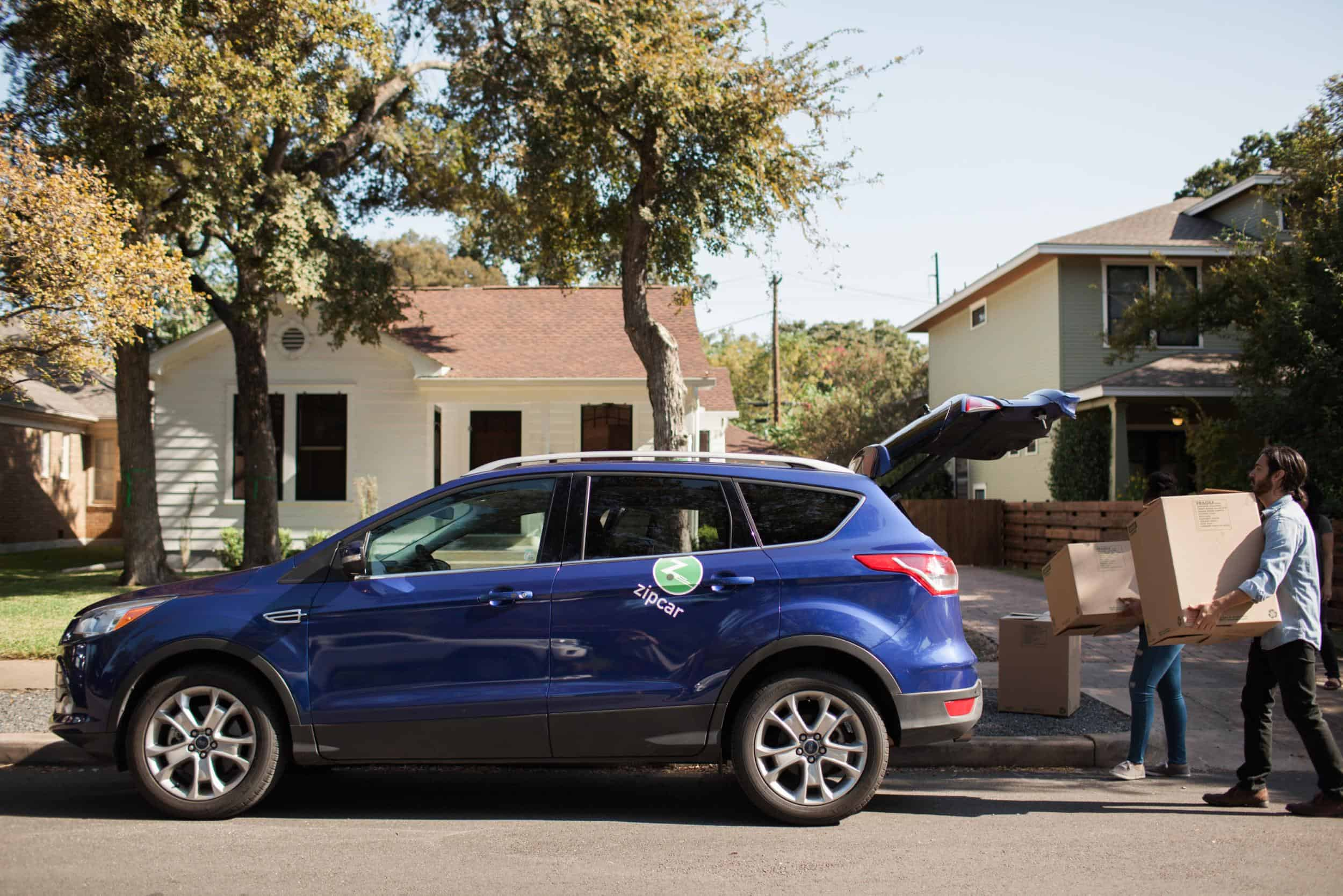 How to live without a car - Blue Zipcar and people carrying boxes