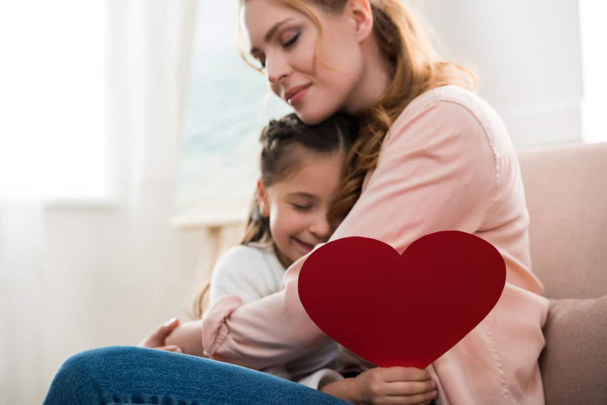 Mother and daughter embrace with homemade heart card