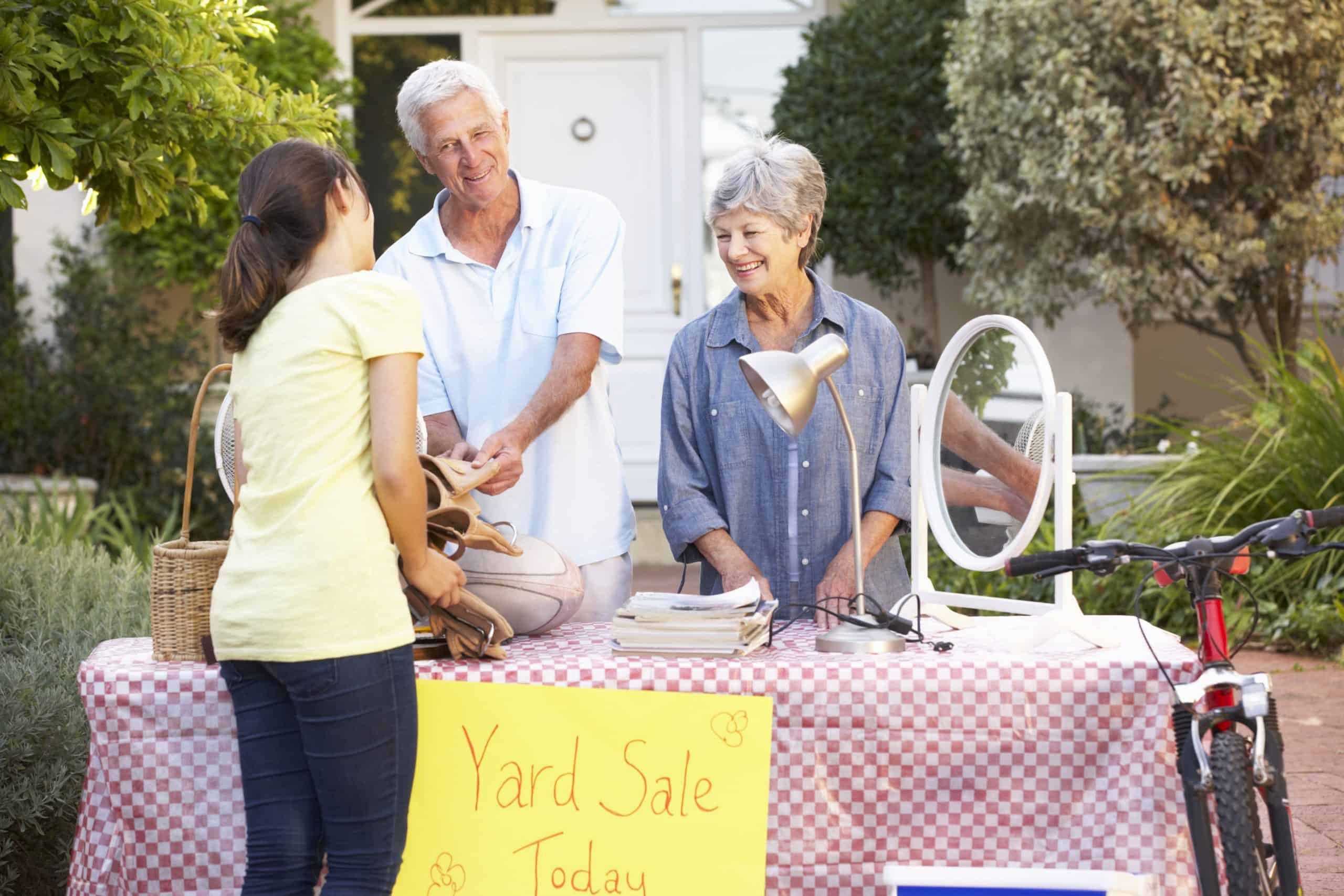 Make money with garage sales - Older couple behind table with red-and-white checkered tablecloth and sign saying Yard Sale Today selling to young brunette woman in yellow