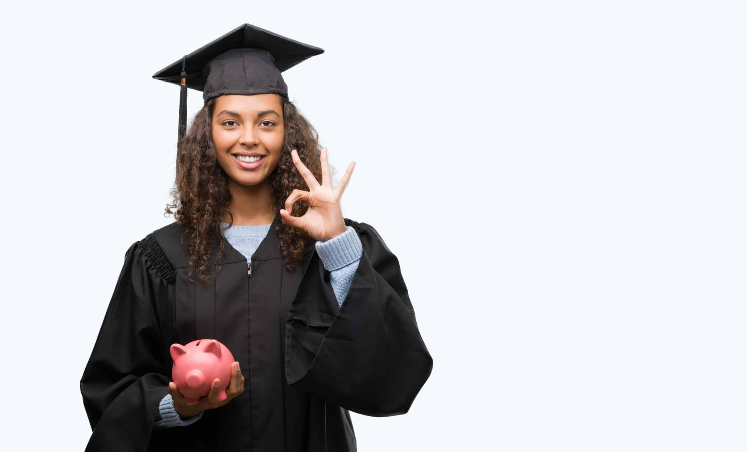 Money tips for graduates - Young hispanic woman wearing graduation uniform holding piggy bank doing ok sign with fingers, excellent symbol