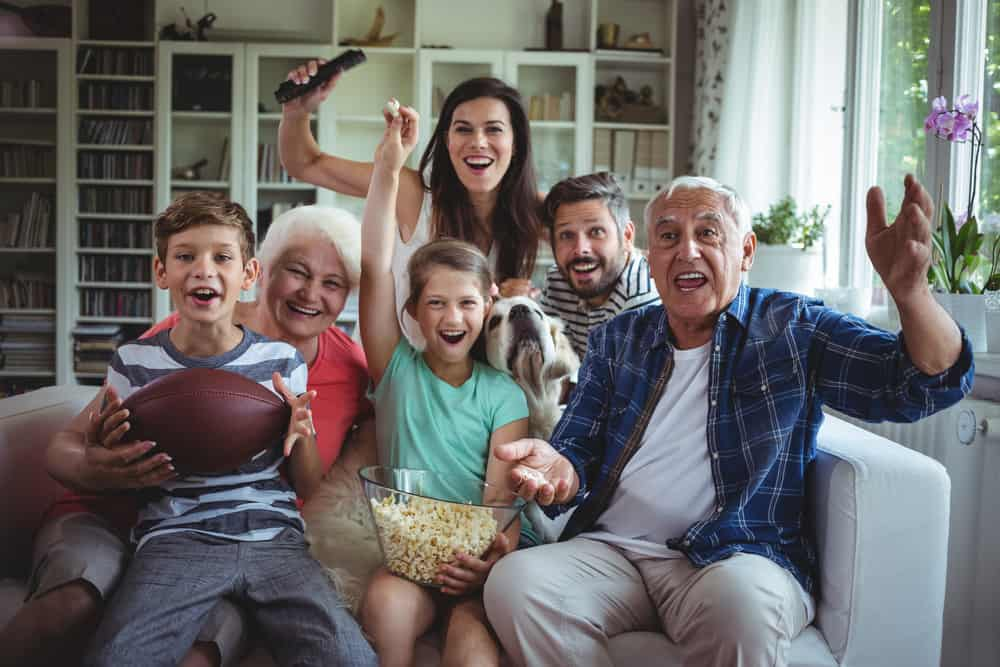 multi-generational family in home cheering on their football team without cable