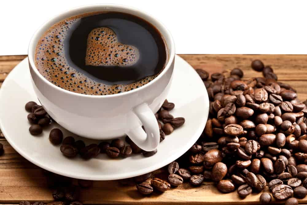 cup of coffee with heart in the liquid, surrounded by coffee beans