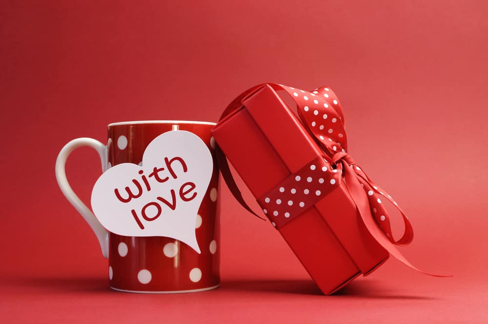 """A red mug with white hearts, with a tag that says """"with love,"""" next to a red gift box wrapped in red and white ribbon."""