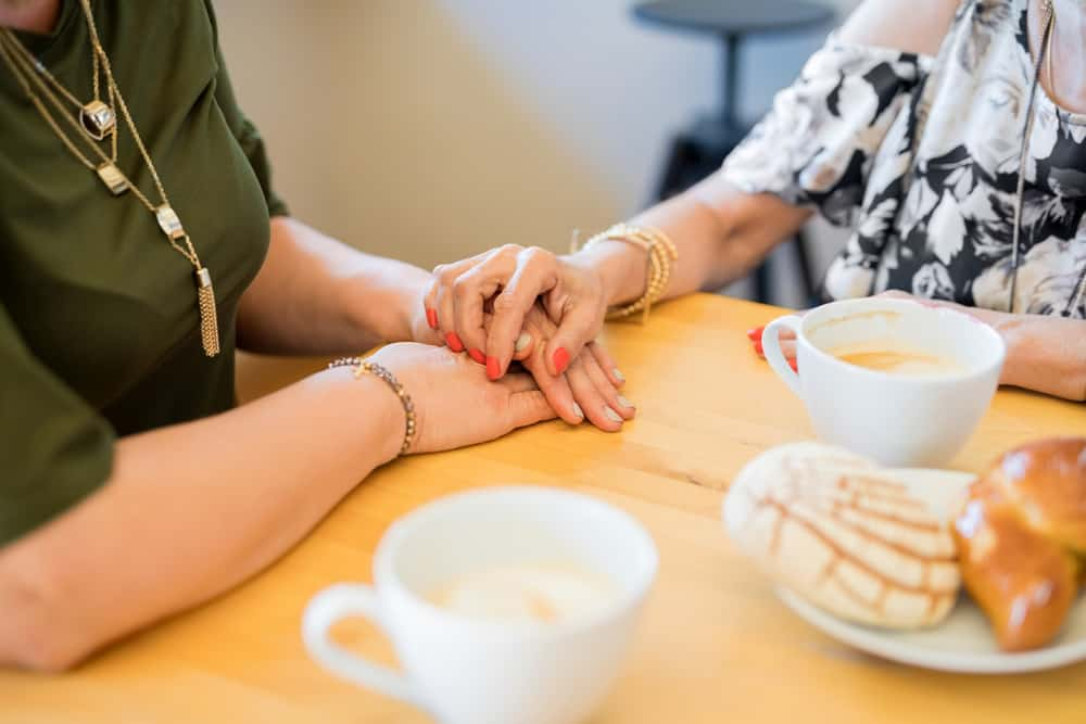 Mothers Day gift ideas - woman and daughter holdign hands over coffee