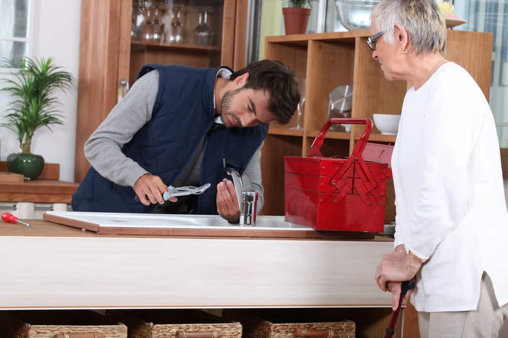 Home repairs - Man fixes faucet for older woman