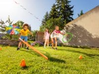 Group of divers kids throwing circles, sports hoops to the target playing game on the lawn