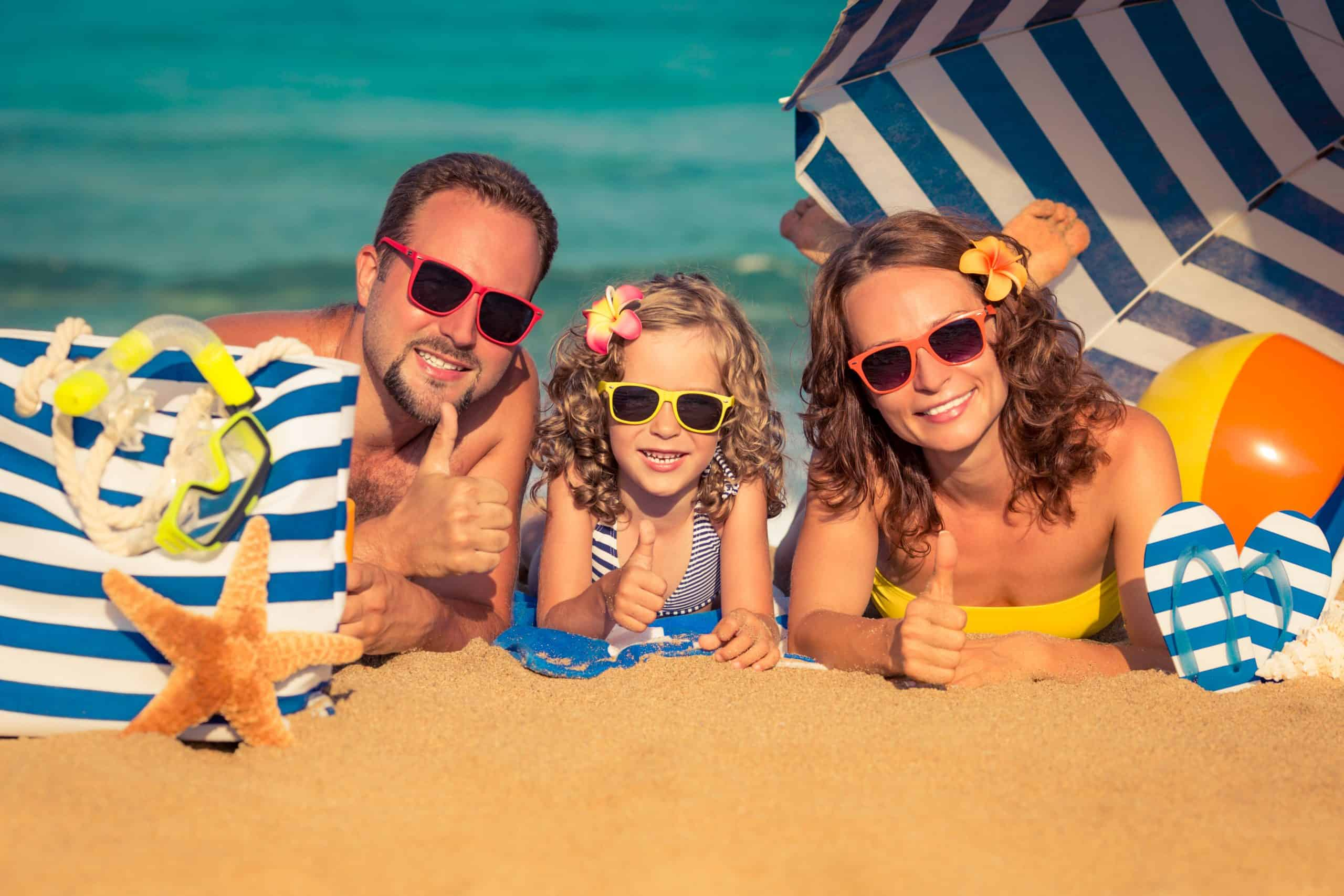 How to save for vacation - dad, girl and mom lying on the beach giving the thumbs up sign