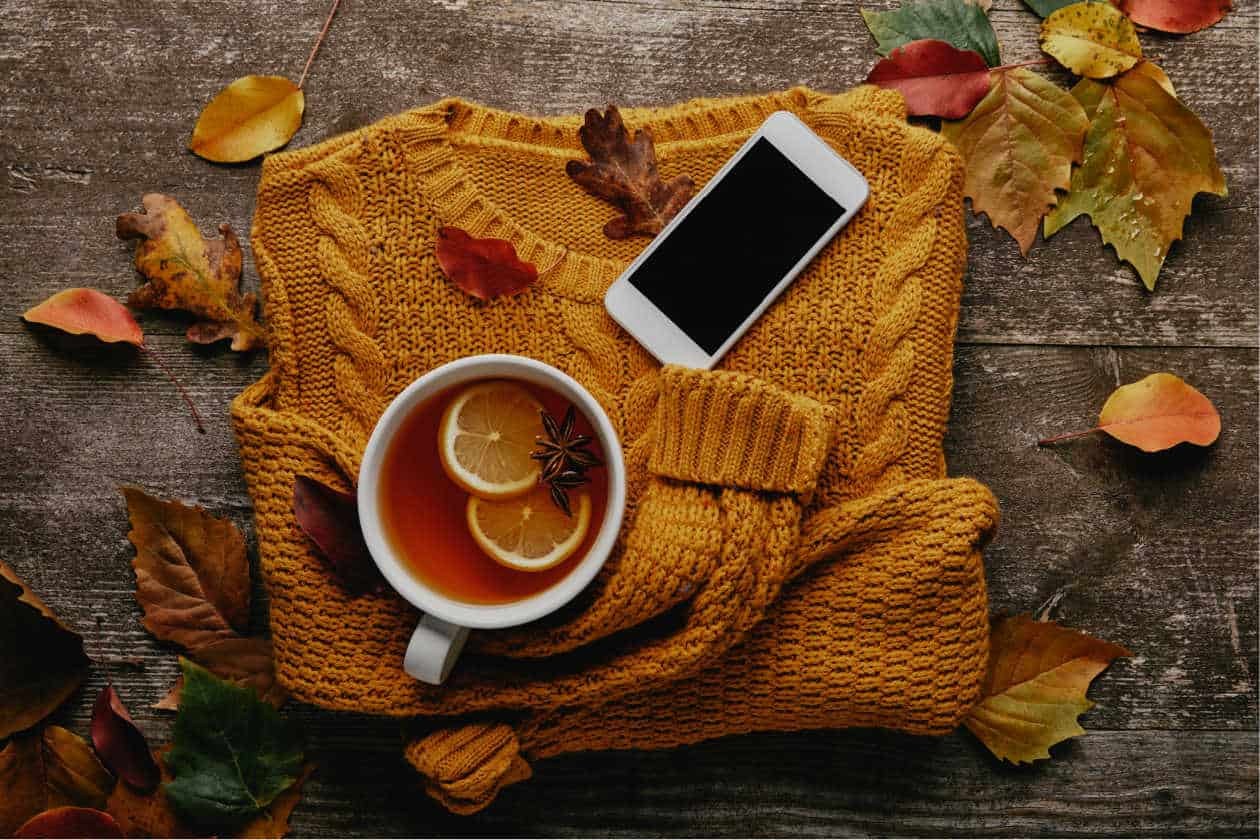 fall outfit sweater with cell phone and warm beverage