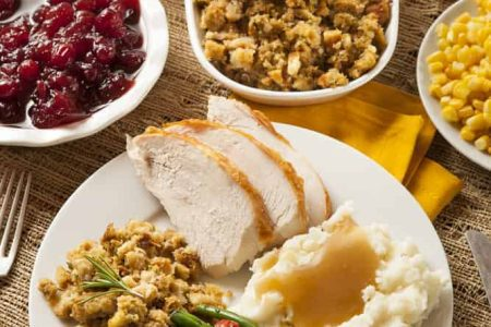 Thanksgiving dinner with all the traditional sides - turkey, mashed potatoes, gravy, green beans, stuffing, cranberries