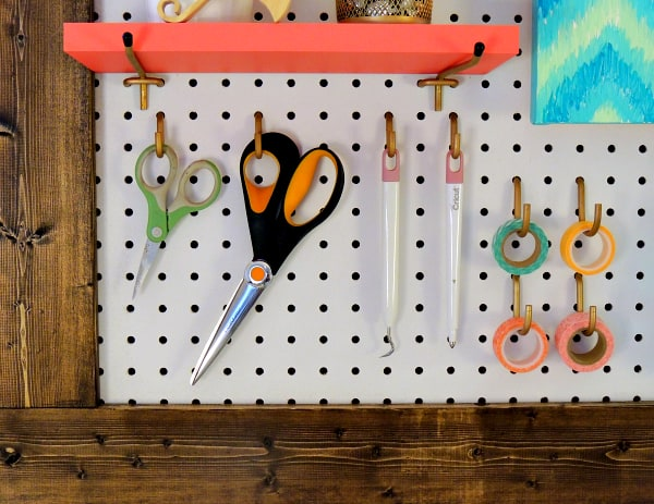 framed pegboard with office supplies hanging from it