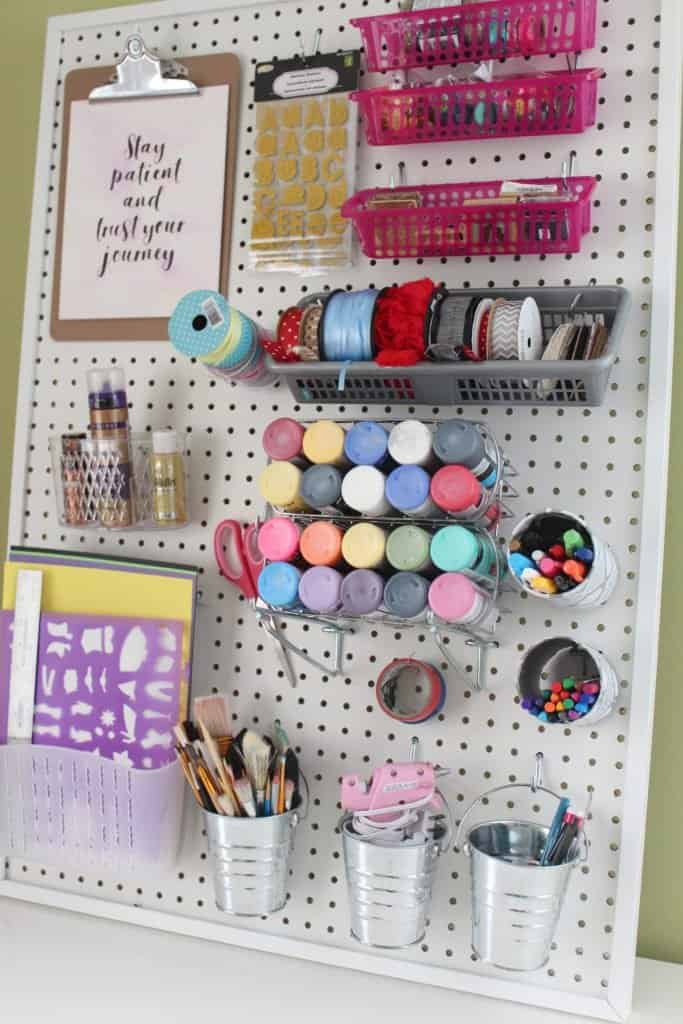 White framed pegboard with dollar store accessories and craft supplies