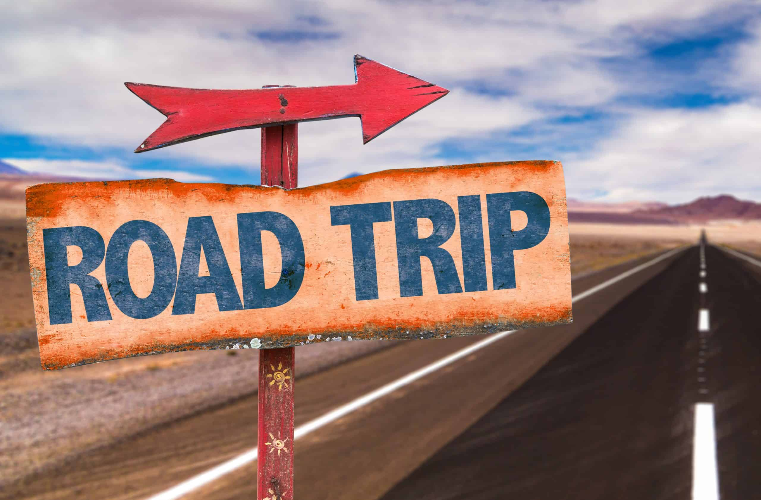 Save money on road trips - empty highway with sign saying road trip and arrow