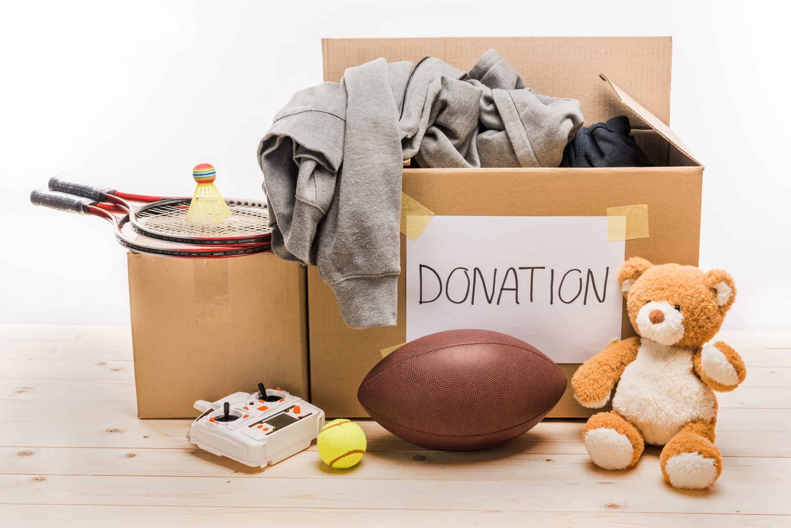 Declutter your home - Box labeled for donation with old shirts, football, badminton racket and teddy bear