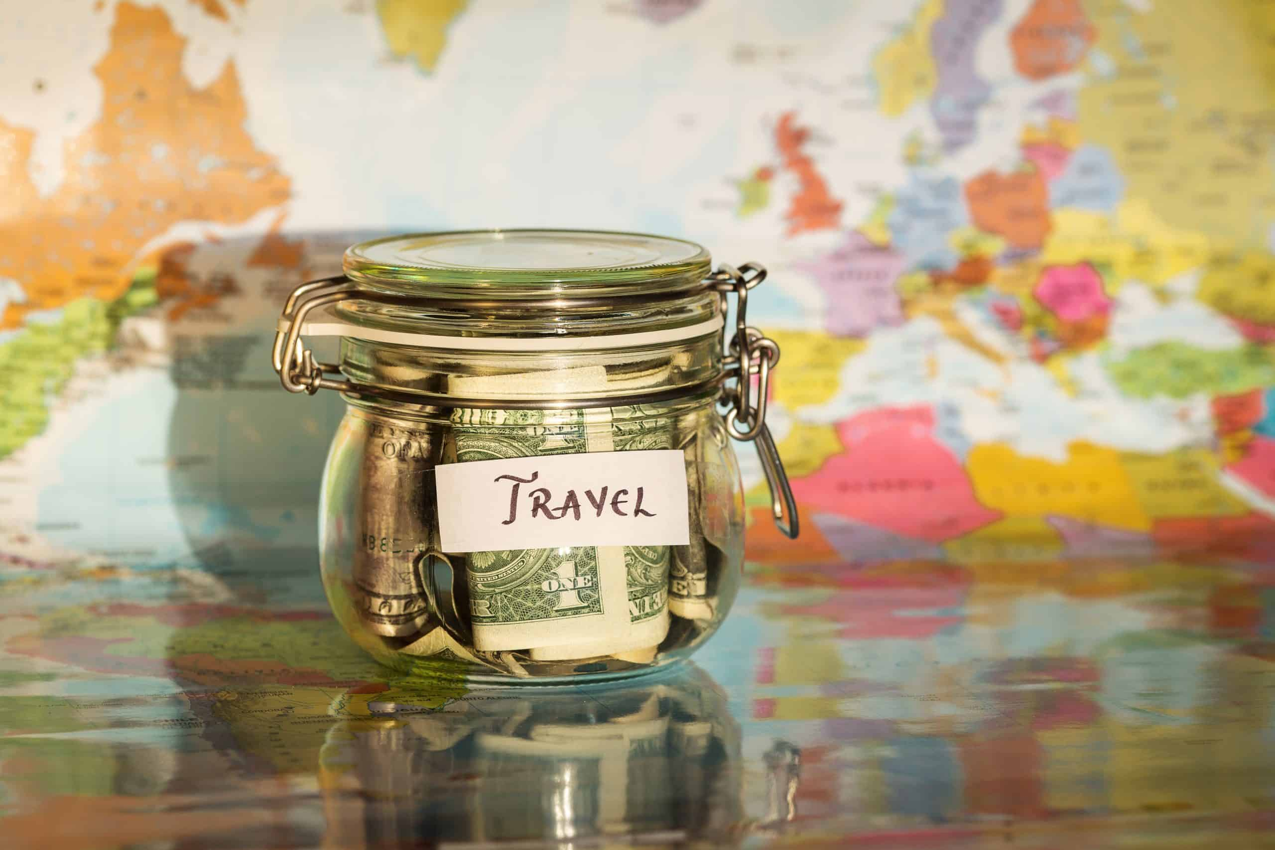 """Save up for vacation - Jar of money with """"travel"""" label against the map of the world"""