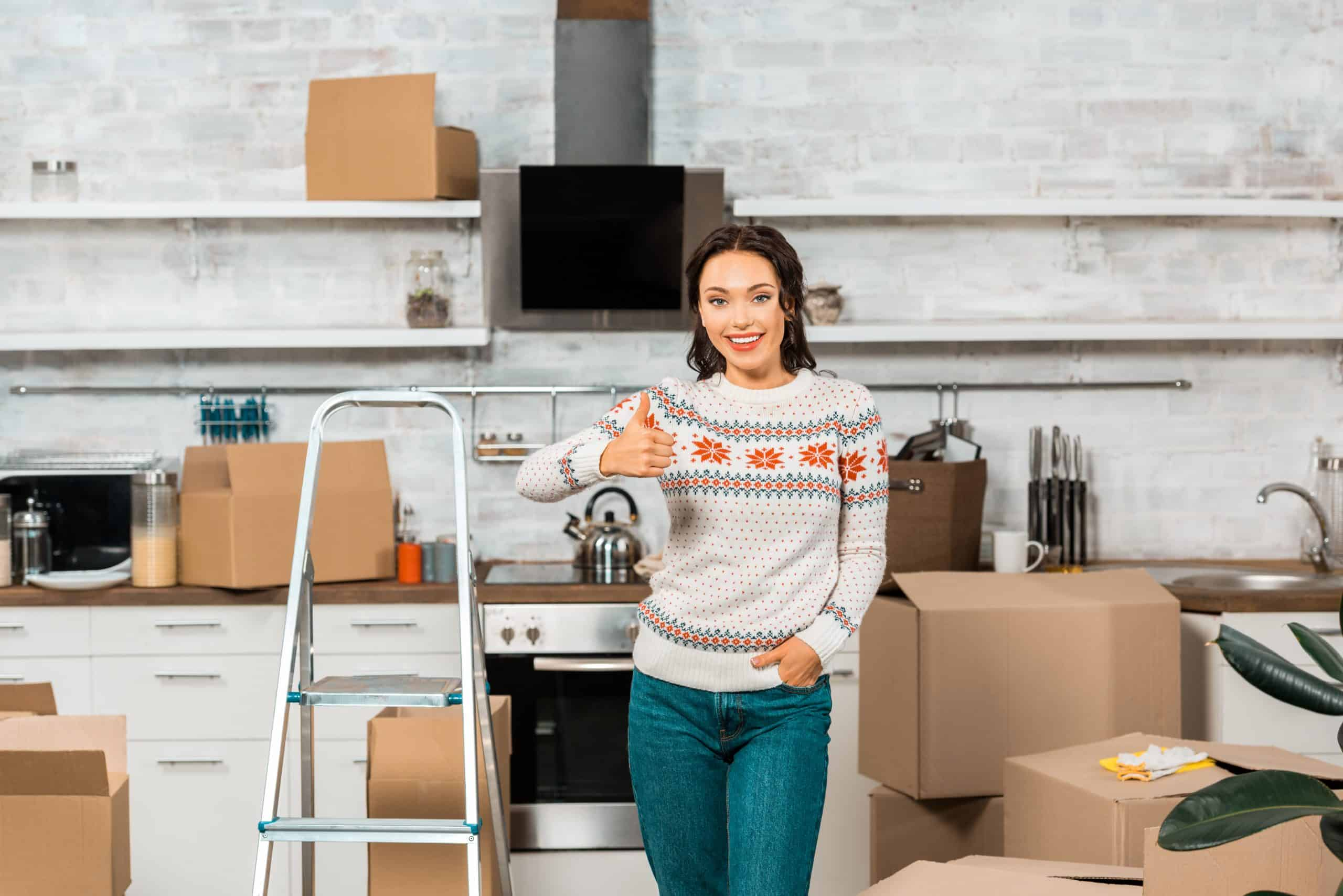 Declutter your home - Woman in kitchen with boxes giving the thumbs up