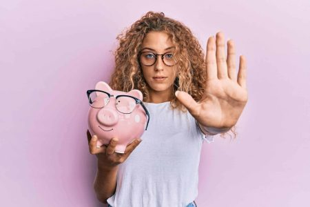 No spend month challenge - Woman holding piggy bank signaling stop